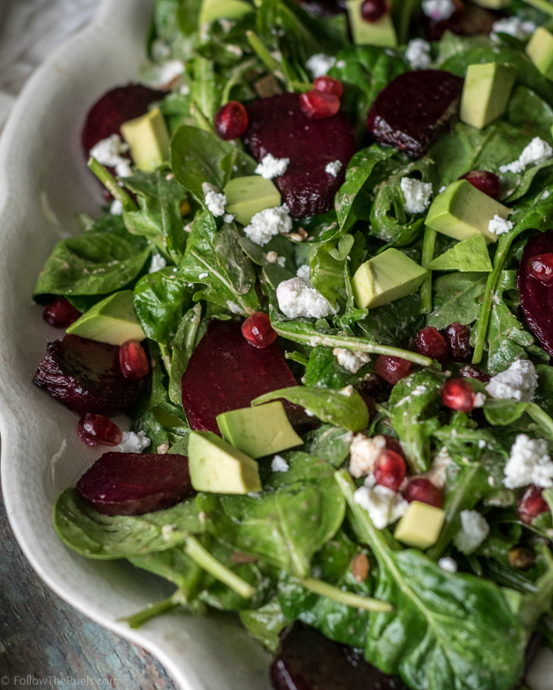 Healthy beet salad topped with avocado, goat cheese, and pomegranate